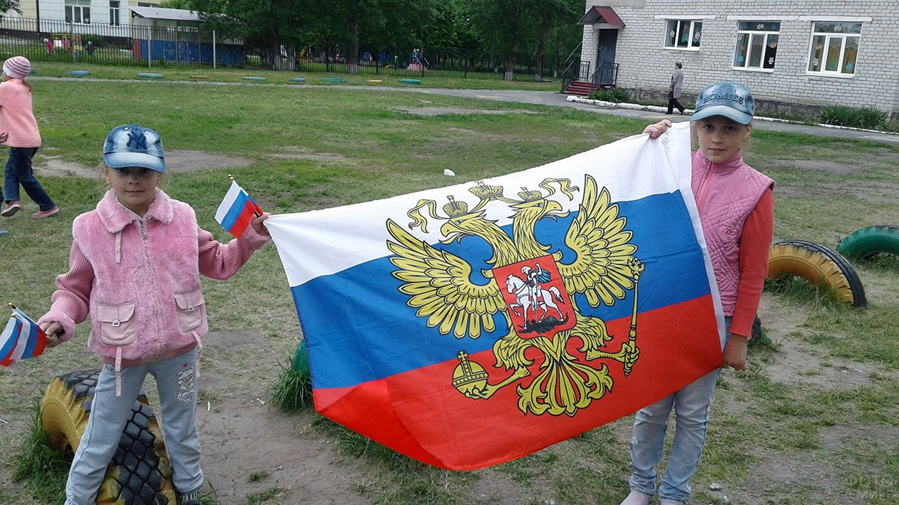 Девочки с флагом во дворе школы в Тюменской области