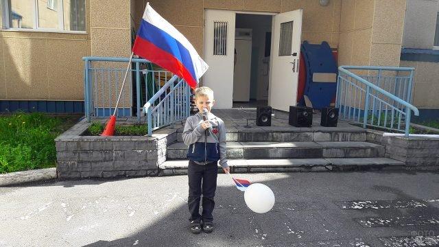 Мальчик выступает на крыльце детского сада на концерте в честь Дня России