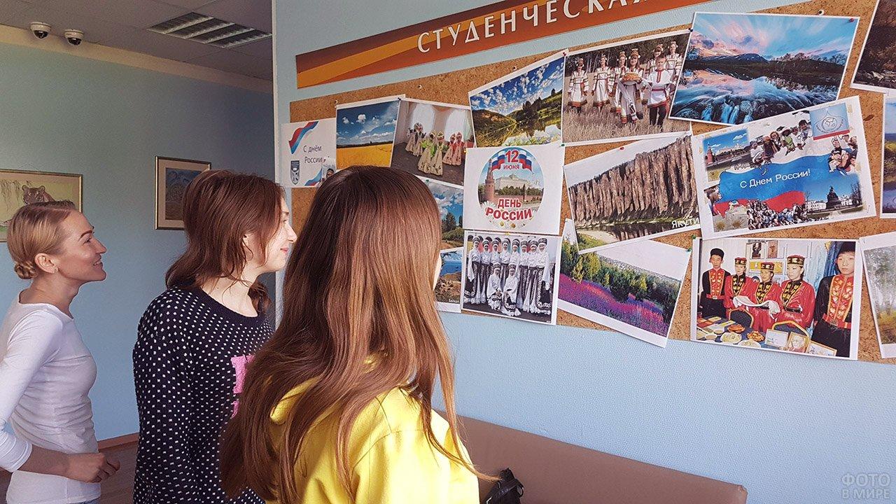 Студентки и преподаватель Тюменского колледжа у стенда в честь Дня России
