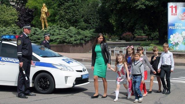 Дети с учительницей переходят дорогу перед машиной ГИБДД под присмотром инспекторов