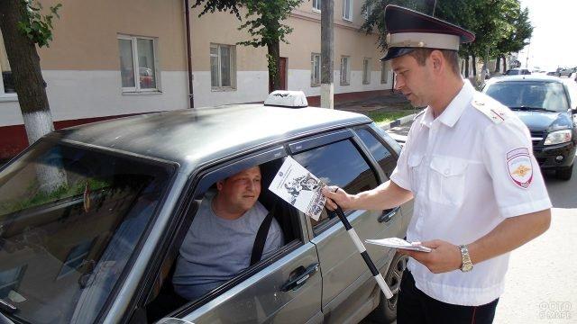 Инспектор ГИБДД в свой профессиональный праздник вручает памятку водителю
