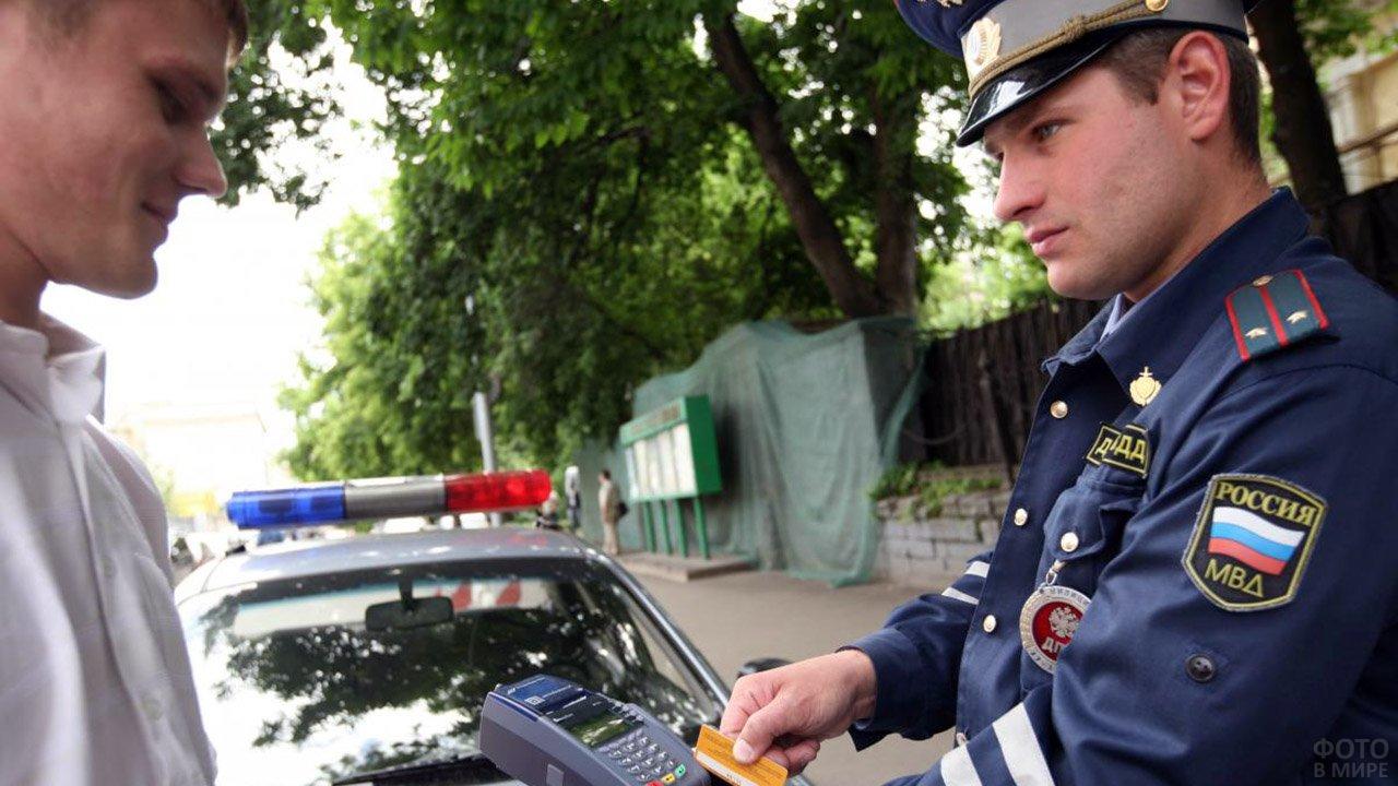 Проштрафившийся автолюбитель и инспектор ГИБДД с терминалом оплаты картой в руках
