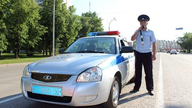 Сотрудник ДПС у патрульной машины на улице Кемерово