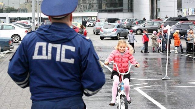 Сотрудник Госавтоинспекции присматривает за маленькими велосипедистами