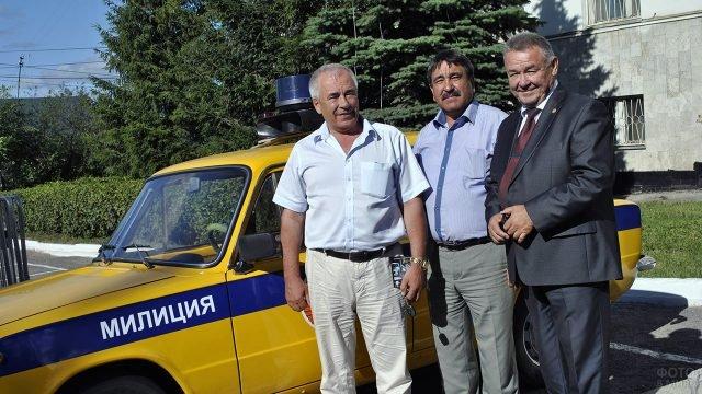 Бывшие сослуживцы в День 80-летия ГАИ на фоне патрульного ретромобиля
