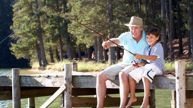 Дед с внуком ловят рыбу с деревянного пирса