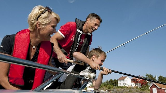 Моложавые дедушка и бабушка учат внука ловить рыбу