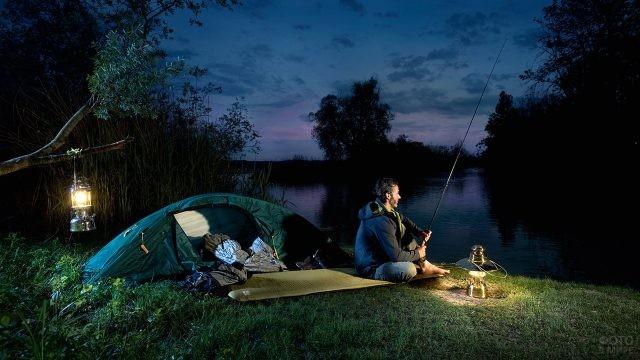 Мужчина на ночной рыбалке с палаткой и походными керосинками