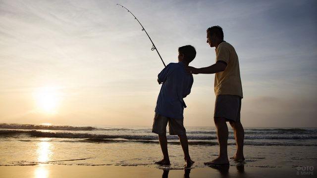 Отец с сыном на рыбалке ранним утром на берегу моря