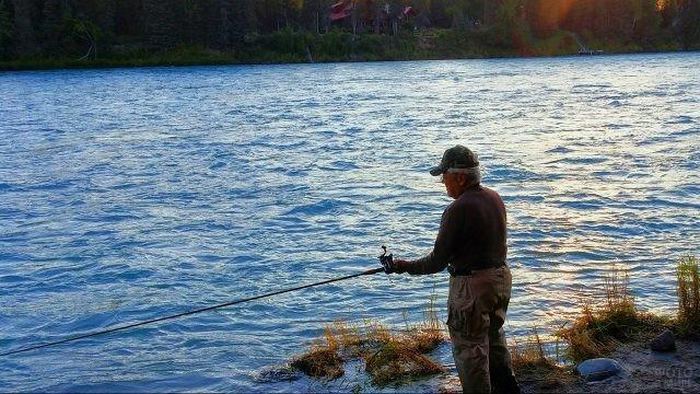 Пенсионер со спиннингом на берегу лесной речки