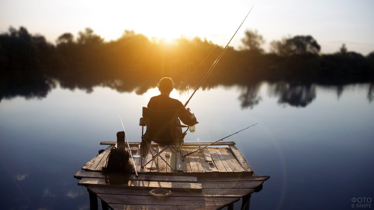 Рыбак на деревянном пирсе над деревенской речкой