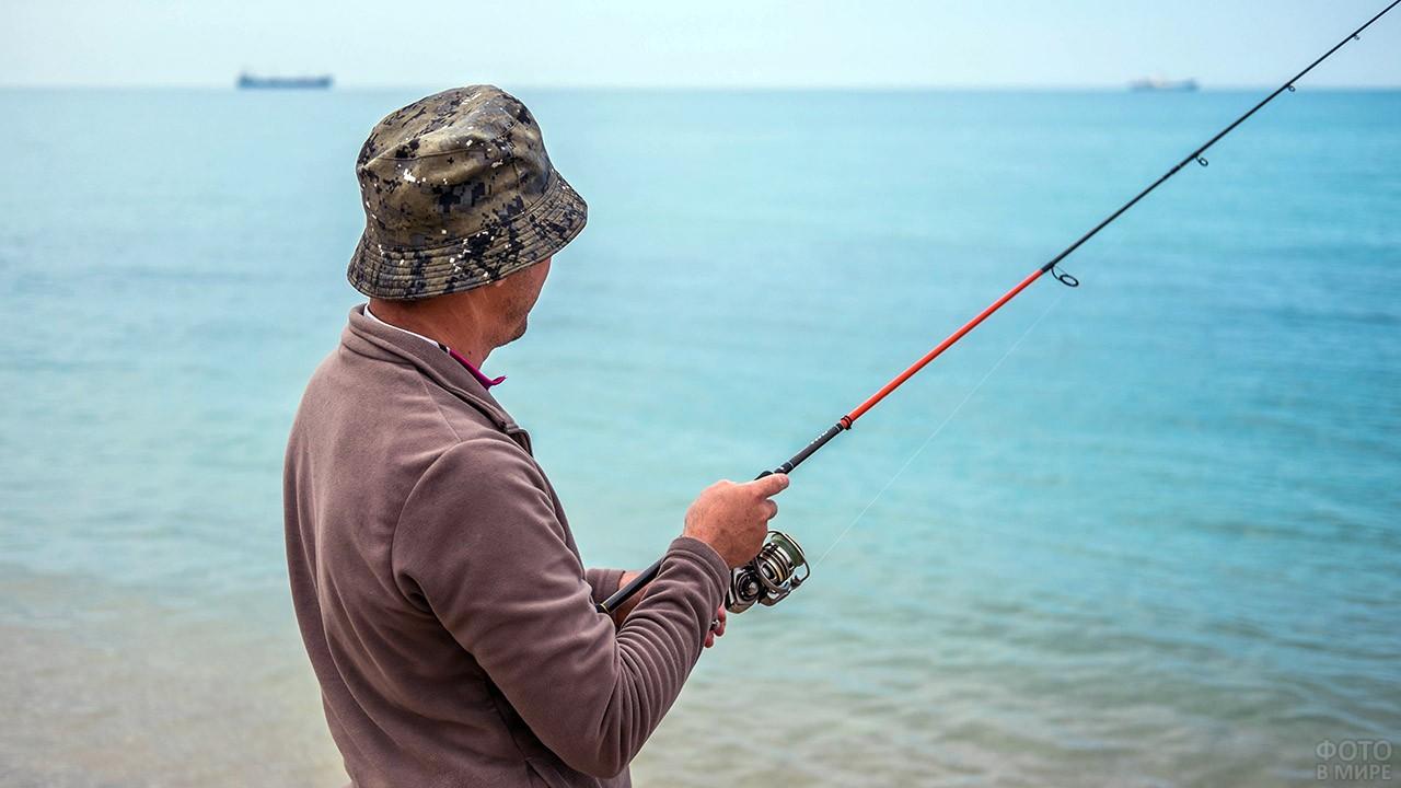 Рыбак в панаме на морском берегу
