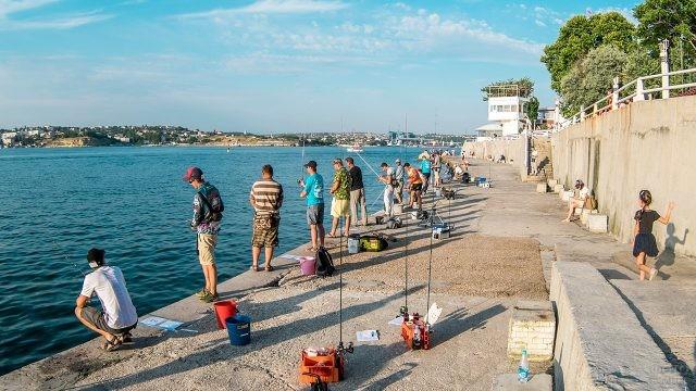 Рыбаки на морской набережной