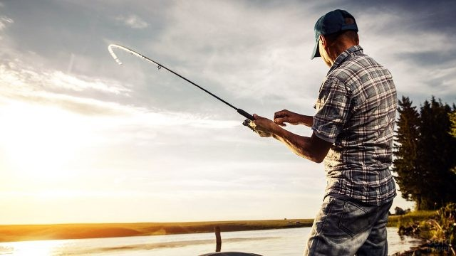 Рыболов на берегу речки в лучах утреннего солнца