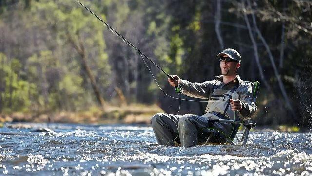 Рыболов с комфортом расположился в кресле на мелководье речки