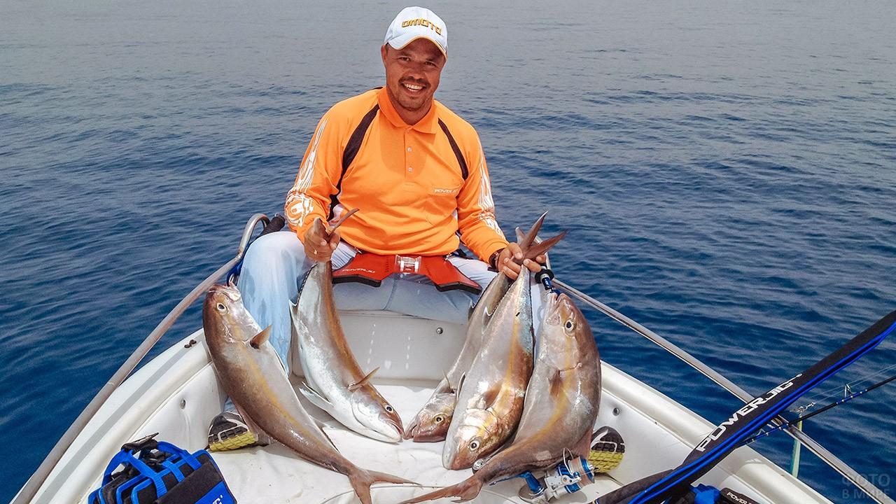 Счастливый рыбак с уловом на носу лодки посреди моря
