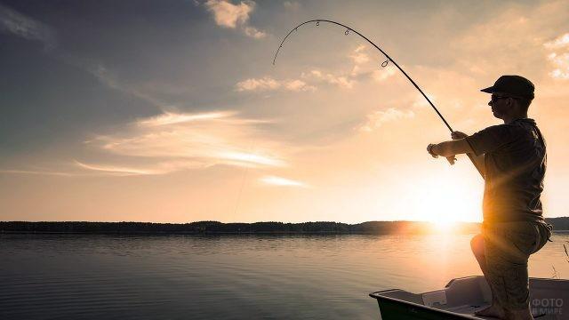 Силуэт рыбака на фоне рассвета над озером