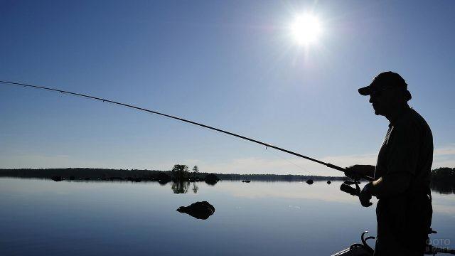 Силуэт рыбака на озере