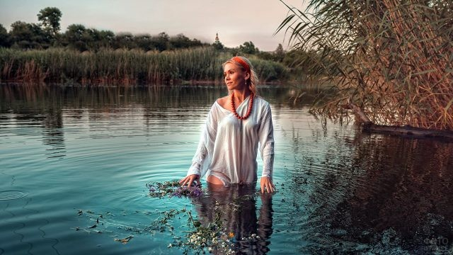 Блондинка в бусах с алой лентой в волосах в речке вечером на Ивана Купалу