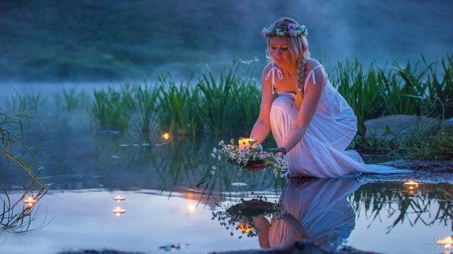 Девушка опускает в реку венок со свечой в ночь на Ивана Купалу