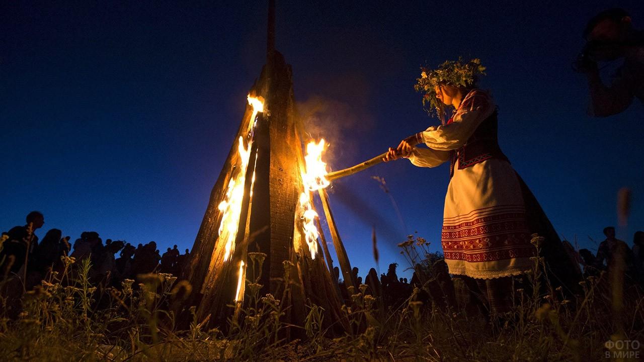 Девушка в национальном костюме зажигает костёр в ночь на Ивана Купалу