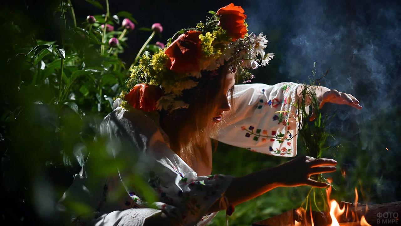 Девушка в венке ворожит над лесным костром в ночь на Ивана Купалу