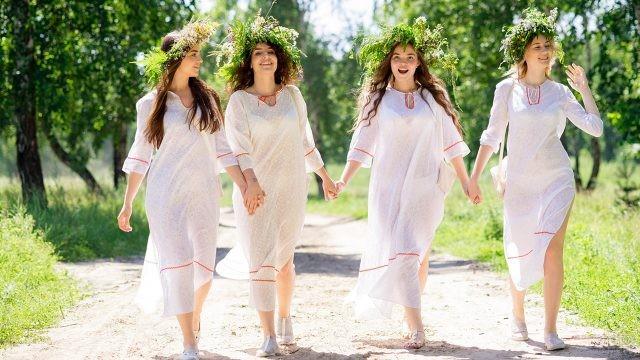 Девушки в белых нарядах и венках идут по лесной тропинке в день Ивана Купалы