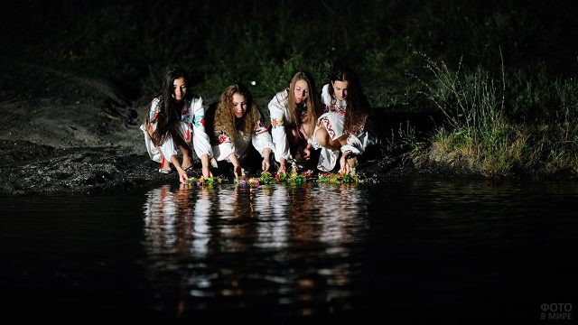 Девушки в национальных костюмах опускают в реку венки в ночь на Ивана Купалу