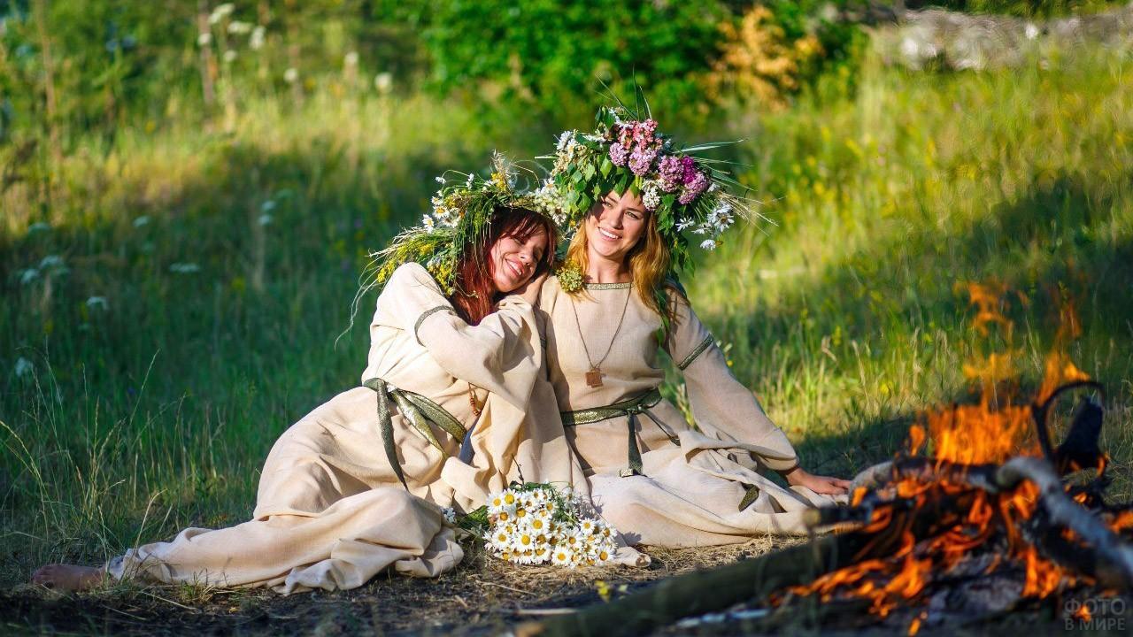 Две славянки в венках у лесного костра в день Ивана Купалы