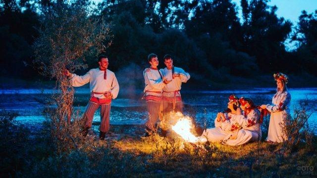 Юноши и девушки в национальных костюмах на берегу реки в ночь на Ивана Купалу