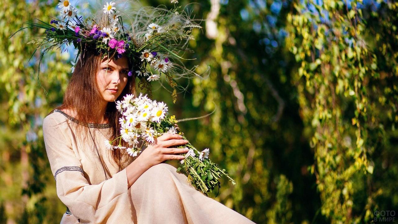 Красивая славянка в венке с букетом ромашек в день Ивана Купалы