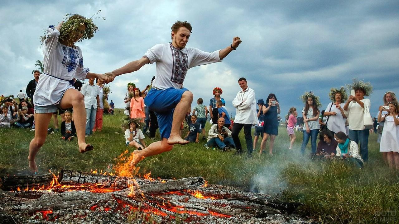 Парень с девушкой прыгают через костёр на Ивана Купалу