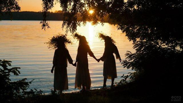 Силуэты девушек в венках на фоне заката над рекой на Ивана Купалу