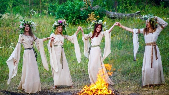 Славянки в венках танцуют вокруг лесного костра в день Ивана Купалы