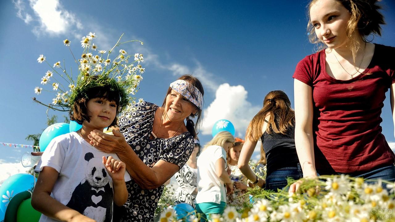 Бабушка с внучкой примеряют венок из ромашек в День семьи, любви и верности