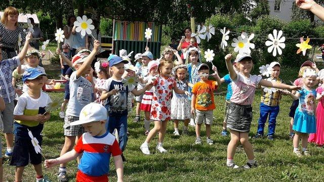 Дети танцуют с бумажными ромашками - символами Дня семьи, любви и верности
