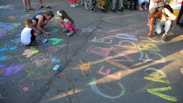 Дети участвуют в конкурсе рисунков на асфальте в День семьи