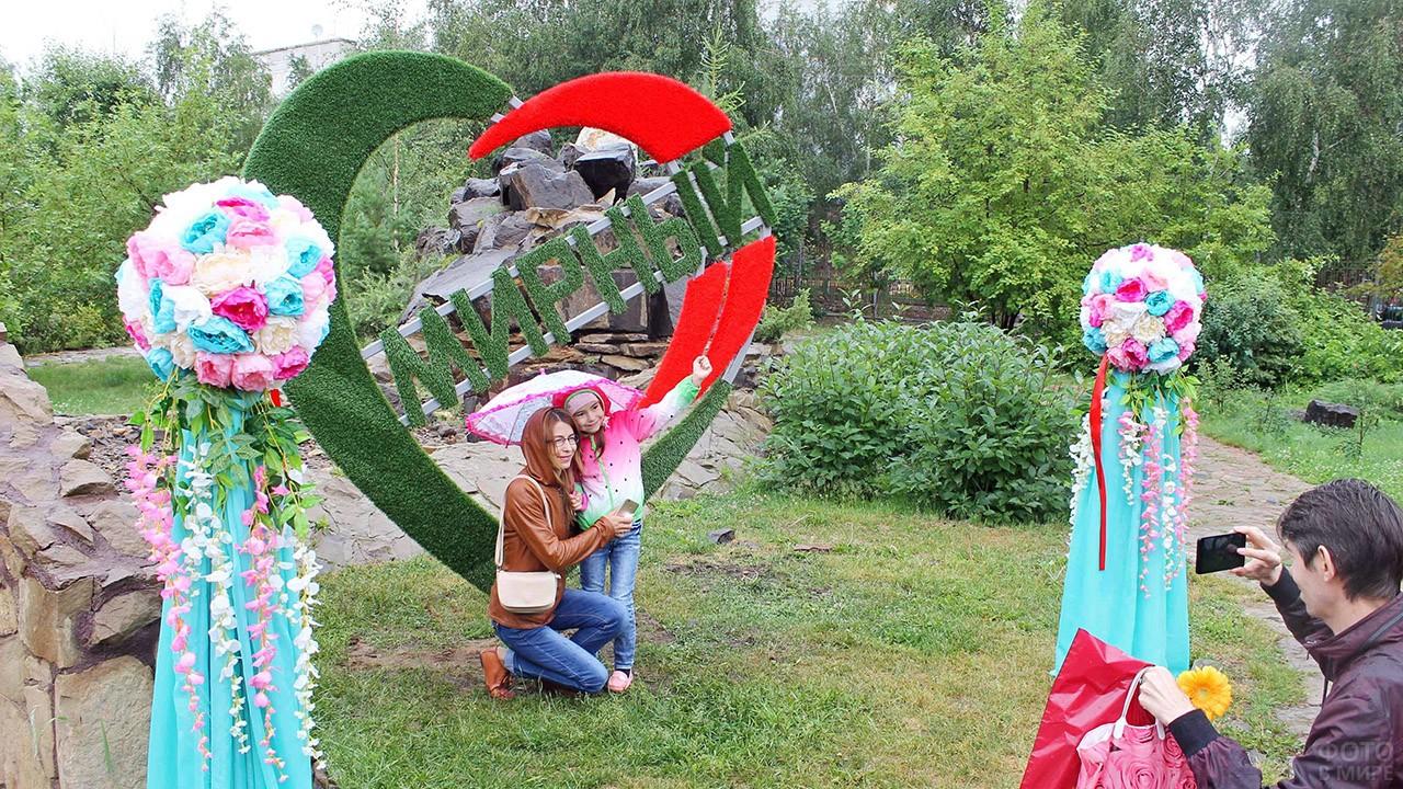 Мама с дочкой в фотозоне в День семьи, любви и верности в Мирном