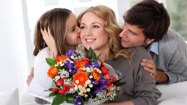 Папа, дочка и мама с букетом цветов в День семьи, любви и верности