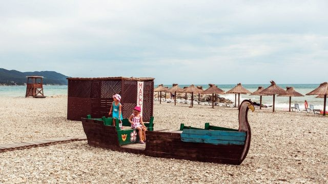 Девочки на игровой площадке в виде лодки на пляже