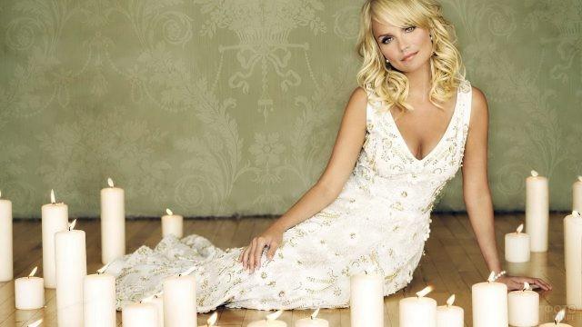 Актриса в белом платье среди горящих свечей