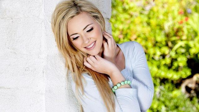 Блондинка облокотилась на стену