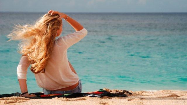 Блондинка поправляет волосы на пляже