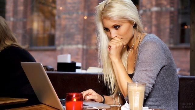 Блондинка в наушниках смотрит в ноутбук в кафе