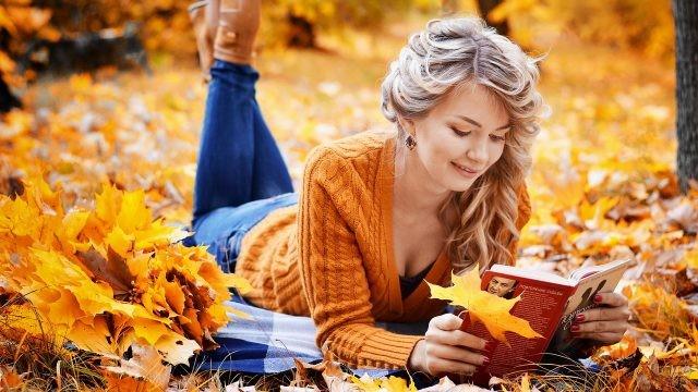 Читающая девушка на покрывале в осеннем парке