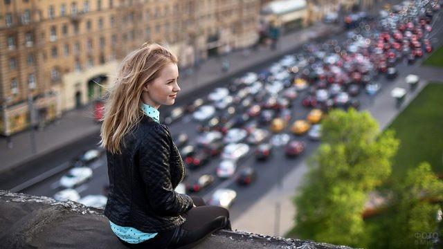 Девушка на крыше на фоне автомобильной пробки