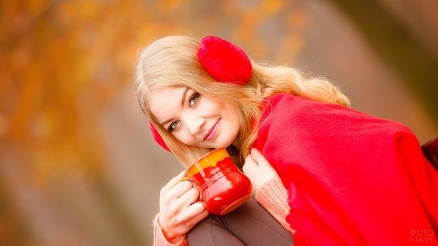 Девушка под красным пледом пьёт из кружки