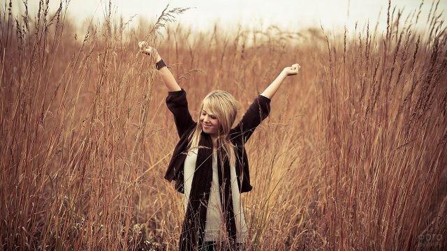 Девушка потягивается среди высокой сухой травы