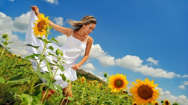 Девушка в белом сарафане в поле подсолнухов