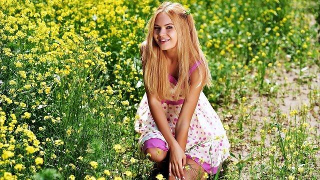 Девушка в ярком сарафане на цветочном лугу